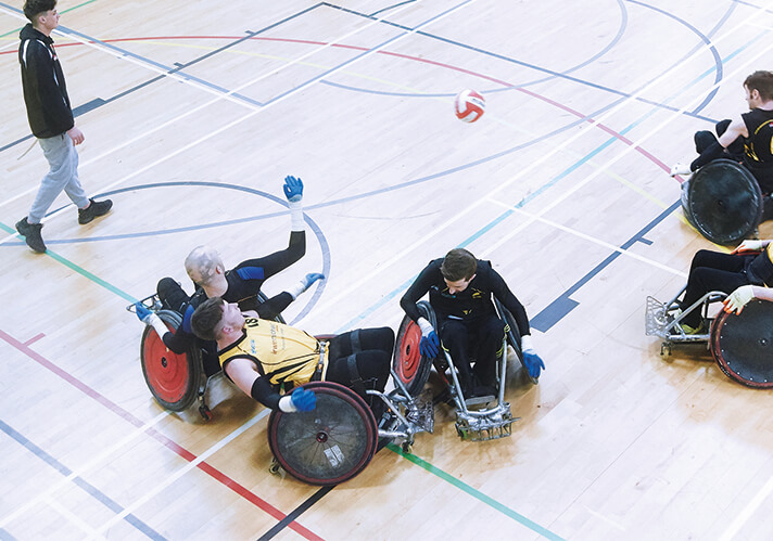 players contesting the ball in a wheelchair rugby match